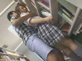 Ujo koulutyttö haparoi ja used sisään a kirjasto