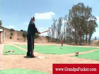 Old man showing a lady how to swing