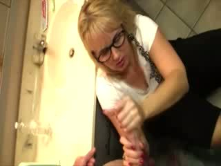 Naughty granny takes a cock in her hands in the bathroom