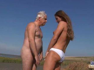 Mladý busty goddess na koni starý člověk v a divoký souložit na the pláž