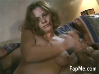 Naughty hot MILF is on the sofa giving her lucky man a nice handjob