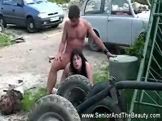 Busty bruneta gets fucked proti an starý auto podle antický dude
