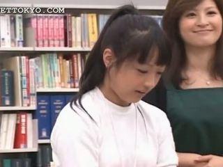 Brunette asiatique fille seducing son étudiante en la bibliothèque